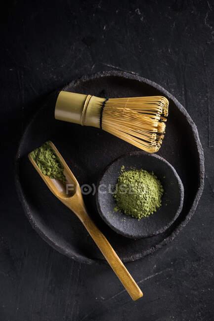Löffel mit getrockneten Matcha-Teeblättern auf schwarzem Geschirr mit Chasen für traditionelle orientalische Zeremonie — Stockfoto