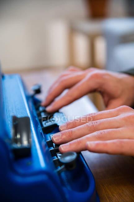 Crop anónimo discapacitado visualmente mecanografía masculina en la máquina de escribir con sistema de escritura táctil en casa - foto de stock