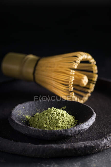 From above of dried tea leaves in heap on plate with chasen for tea ceremony — Stock Photo