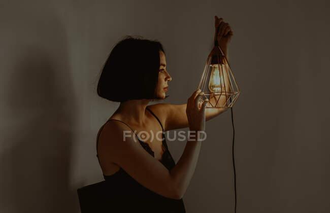 Vista laterale di delicata femmina toccando lanterna metallica illuminata mentre seduto in camera a casa — Foto stock