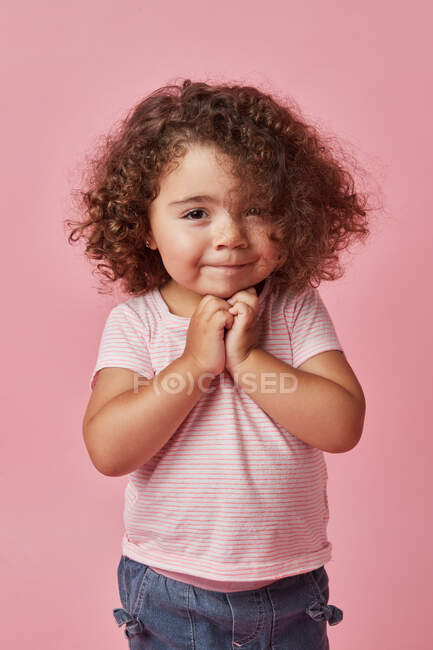 Cute happy toddler girl with curly hair in casual clothes looking at camera on pink background — Stock Photo
