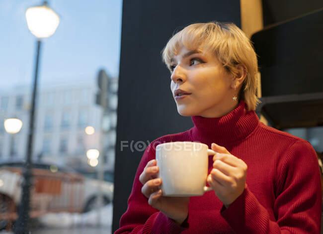 Задумчивая молодая женщина в уютном красном свитере наслаждается ароматным горячим напитком, сидя на удобном кресле в кафетерии и мечтательно отворачиваясь — стоковое фото