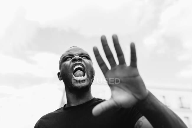 Desde abajo negro y blanco de joven macho étnico enojado gritando y mostrando gesto de alto mientras mira hacia adelante en la ciudad - foto de stock