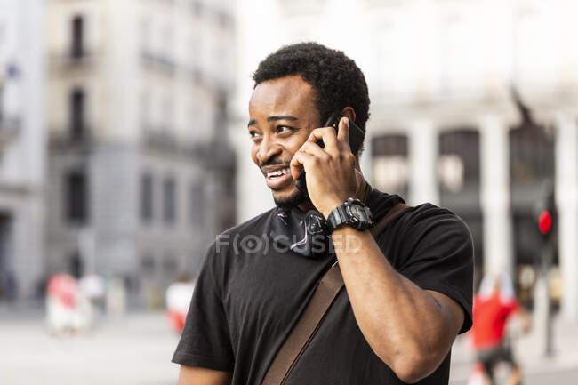 Молодой афроамериканец в наручных часах разговаривает по мобильному телефону, глядя в город — стоковое фото
