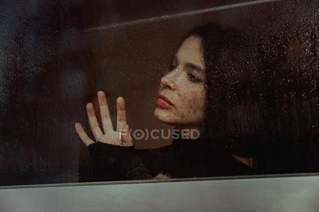 Através de vidro de fêmea pensativa em pé perto da janela e observando a rua enquanto olha para longe — Fotografia de Stock