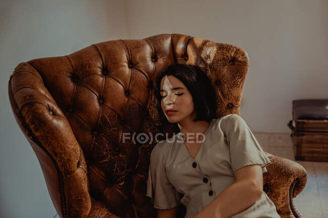 From above of peaceful female sitting in shabby leather chair while relaxing at home with closed eyes — Stock Photo