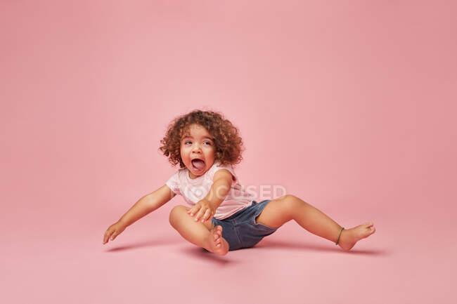Menina da criança alegre bonito com cabelos cacheados em roupas casuais se divertindo fazendo rostos enquanto sentado no chão olhando para o fundo rosa — Fotografia de Stock