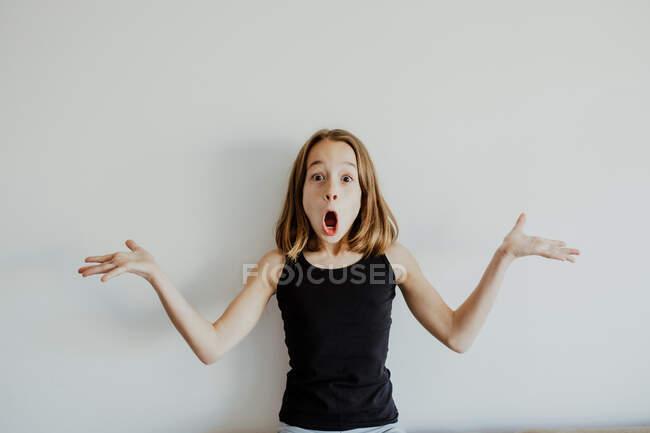 Bambino stupito in abiti casual che scrollano le spalle con la bocca aperta mentre si diverte sullo sfondo bianco — Foto stock