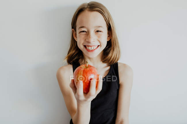 Fröhliches Preteen-Mädchen in lässigem Top lächelt, während es frischen reifen roten Apfel vor weißem Hintergrund beißt — Stockfoto