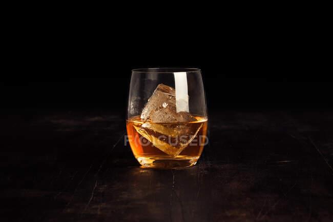 Primer plano de un vaso de té con un cubo de hielo - foto de stock