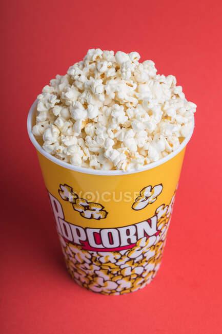 Schüssel voller Popcorn auf rotem Hintergrund — Stockfoto