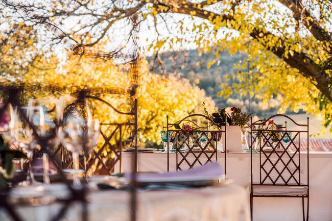 Spacious veranda with plates wineglasses and cutlery placed on tables decorated with fresh flowers for wedding celebration — Stock Photo
