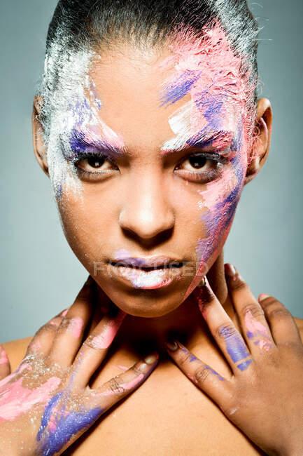 Modello femminile etnico creativo con viso imbrattato di vernice rosa e bianca che tocca il collo guardando la fotocamera su sfondo grigio in studio — Foto stock