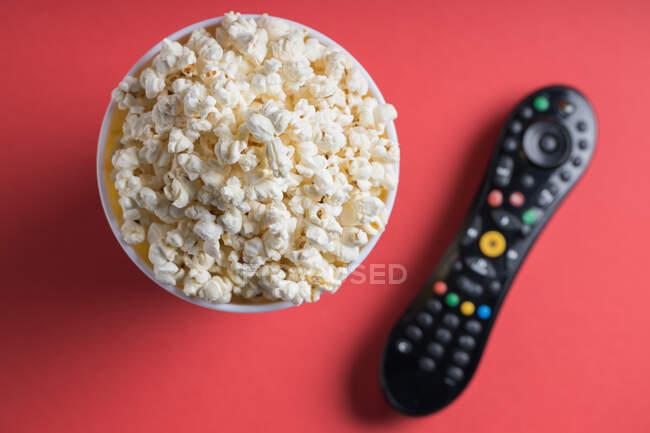 Primo piano di alcuni popcorn su sfondo rosso — Foto stock