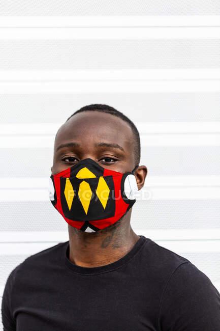 Joven hombre afroamericano mirando a la cámara en máscara brillante con adorno durante el período coronavirus sobre fondo claro - foto de stock
