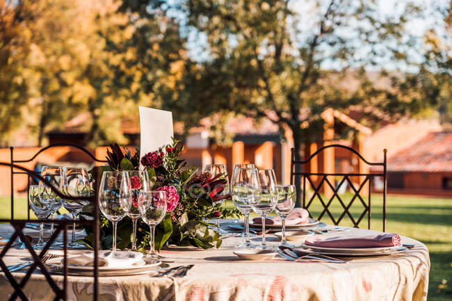 Nahaufnahme der servierten festlichen Tafel mit Kristallgläsern Serviette auf Teller in der Nähe von frischen Blumen für Hochzeit und Menükarte — Stockfoto