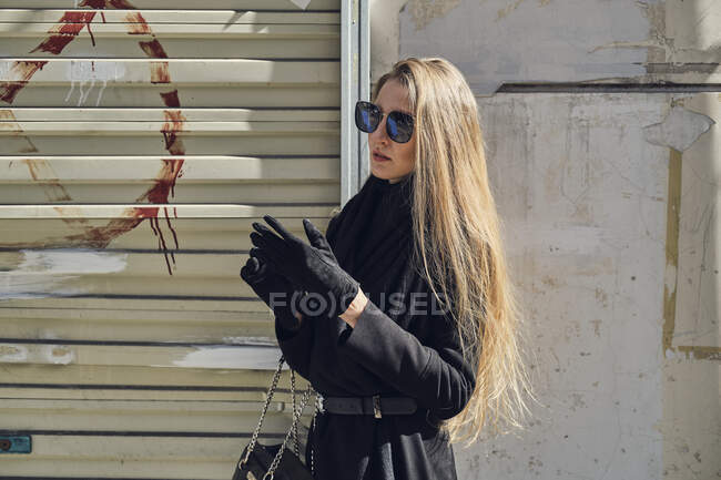 Young blond female in trendy black clothes and gloves near rough walls in town — Stock Photo