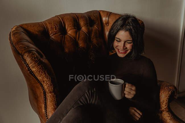 Высокий угол наслаждения женщины, сидящей в потрепанном кожаном кресле с чашкой горячего напитка, улыбаясь и наслаждаясь выходными дома — стоковое фото