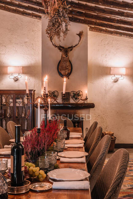 Interior of dining room with wooden table with cutlery and plates decorated with flowers for dinner — Stock Photo
