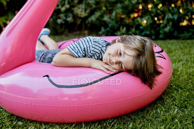 Ragazzino in abiti casual sdraiato su fenicottero rosa gonfiabile mentre si diverte sul prato erboso nel parco — Foto stock