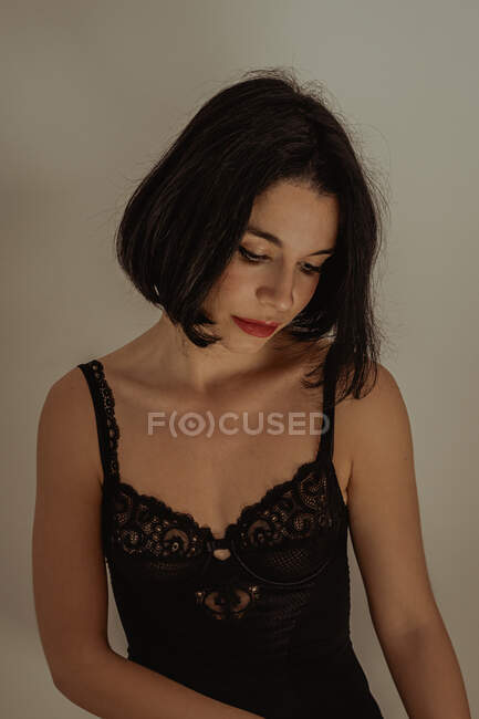 Serene female in black lace bodysuit sitting on stool in room against white wall and looking away — Stock Photo