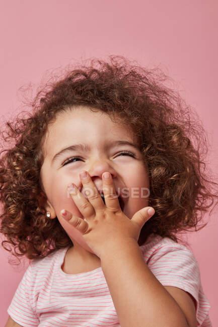 Carino allegro bambino ragazza con i capelli ricci in abiti casual che copre la bocca con la mano, mentre guardando altrove sorridente su sfondo rosa — Foto stock