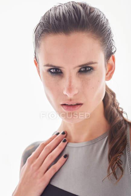Mulher séria com maquiagem e sardas no nariz suavemente e olhando para a câmera — Fotografia de Stock