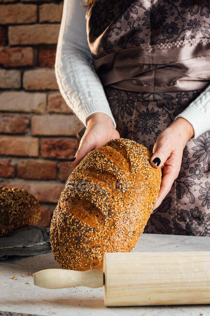 Crop anonymous female baker holding bread with sunflower seeds on table in bakehouse — Stock Photo