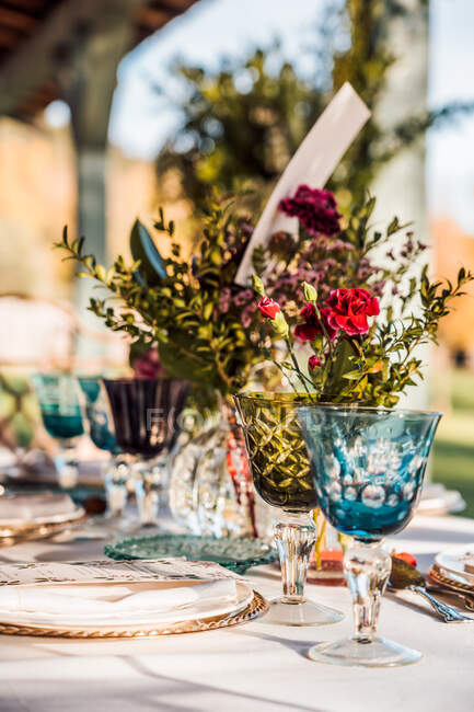 Close-up of served festive table with crystal glasses cutlery napkin on plate near bunch of fresh flowers for wedding — Stock Photo