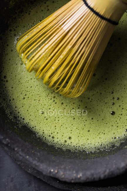 Von oben traditioneller japanischer Matcha mit Teebesen in Steinschale für traditionelle orientalische Zeremonie — Stockfoto