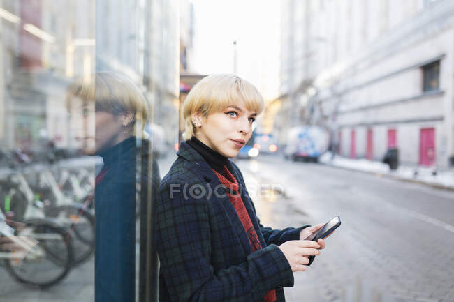 Jeune femme aux cheveux courts en manteau chaud naviguant sur un téléphone portable debout sur une rue enneigée et regardant loin à Madrid, Espagne — Photo de stock