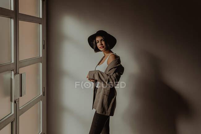 Сторона зору визначена жінка в модному одязі стоячи в кімнаті біля вікна і дивлячись на камеру — стокове фото