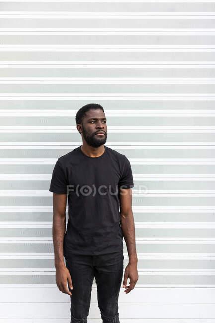 Contenido Hombre afroamericano en camiseta negra de pie mirando a la cámara sobre fondo claro - foto de stock