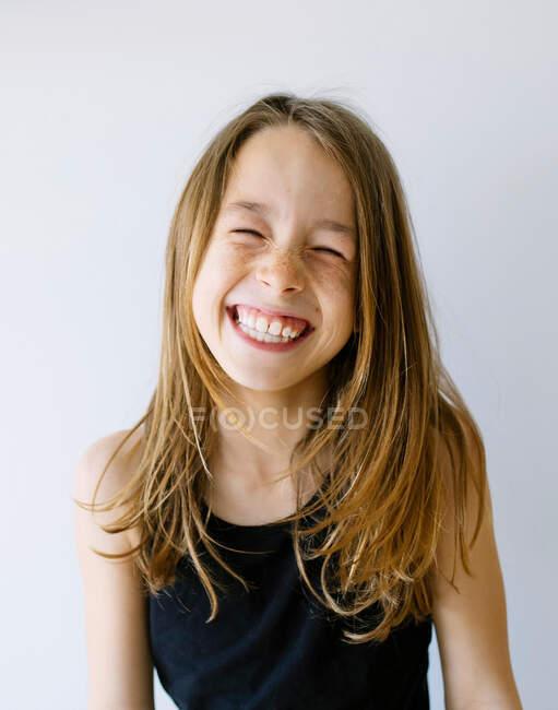 Весела дівчина з світлим волоссям у нижній сорочці з закритими очима радісно сміється на білому фоні — стокове фото