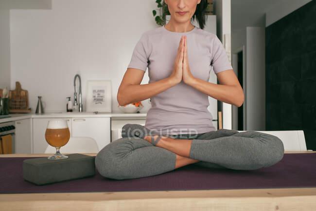 Обрезанная неузнаваемая спокойная женщина, сидящая в позе Лотоса на коврике со стаканом пива и ноутбуком, занимаясь йогой и медитируя на деревянном столе дома — стоковое фото