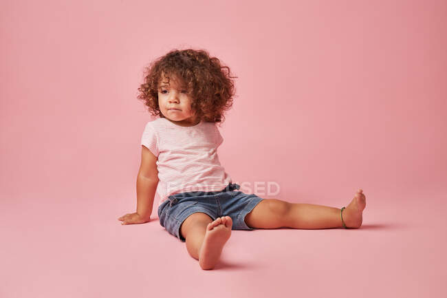Cute thoughtful toddler girl with curly hair in casual clothe looking away while sitting on pink background — Stock Photo