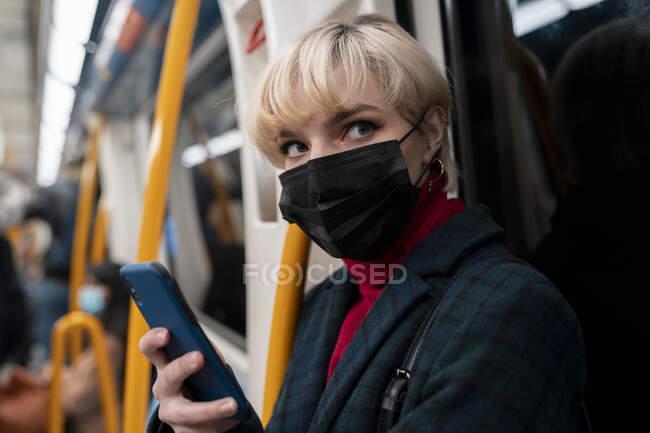 Jovem calmo com cabelo curto em jaqueta quente e máscara protetora navegando telefone celular e olhando para longe ao andar de trem de metrô em Madrid, Espanha — Fotografia de Stock