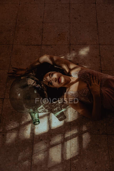 From above of gentle female in dress lying on floor near glass bottle in room with sunlight and looking at camera — Stock Photo