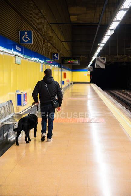 Hombre ciego paseando con perro guía en metro - foto de stock