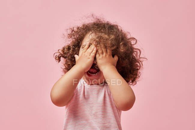 Carino allegra bambina con i capelli ricci in abiti casual che coprono gli occhi con la bocca aperta con la mano sorridente su sfondo rosa — Foto stock