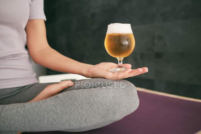 Обрезанная неузнаваемая женщина, сидящая в позе Лотоса на коврике с противоскользящими носками и бокалом пива во время занятий йогой и медитации с жестом мудры дома — стоковое фото
