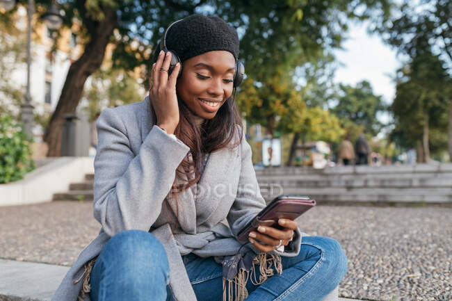 Content African American female in outerwear sitting on street and listening to music in headphones while choosing songs from playlist on smartphone — Stock Photo