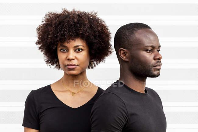 Молода етнічна жінка з африканською зачіскою біля бородатого чоловіка в повсякденному одязі на світлому тлі. — стокове фото