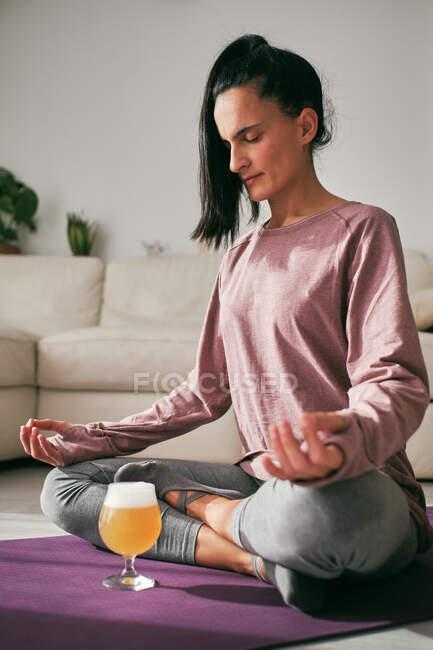 Спокойная женщина сидит в позе лотоса на коврике со стаканом пива и ноутбуком, занимаясь йогой и медитируя дома — стоковое фото
