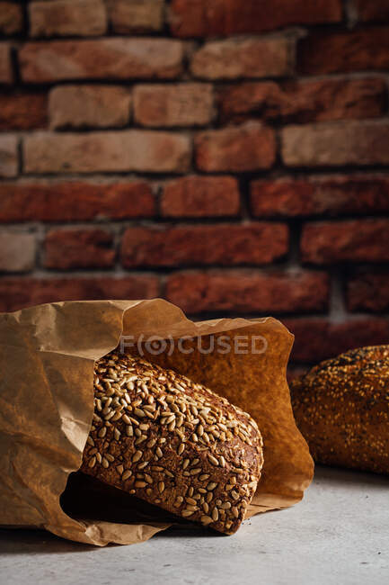 Tasty whole bread with brown crust and sunflower seeds on top on table in daylight — Stock Photo