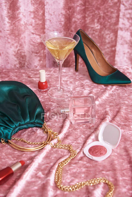 High heeled shoes near handbag and cosmetic products with bottle of perfume and glass of alcoholic drink against velvet curtain — Stock Photo