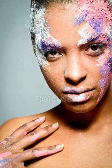Creative ethnic female model with face smeared with pink and white paint looking at camera on gray background in studio — Stock Photo