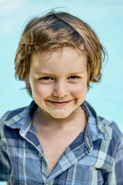 Красивый маленький мальчик с светлыми волосами в стильной клетчатой рубашке улыбается и смотрит в камеру, стоя на синем фоне в солнечном свете — стоковое фото