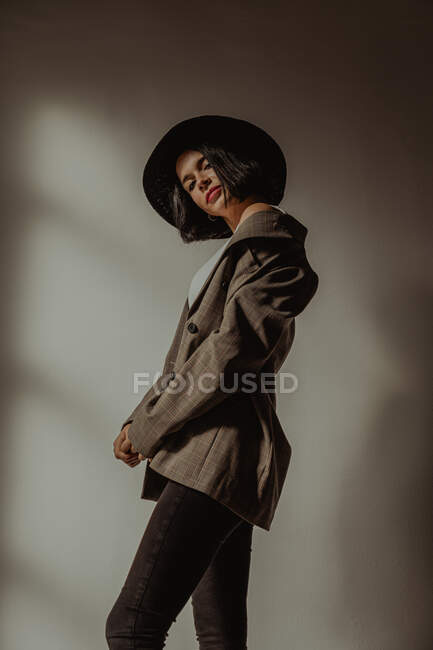 Side view low angle of determined female in trendy outfit standing in room near window and looking at camera — Stock Photo