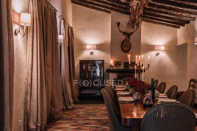 Interior del comedor con mesa de madera con cubiertos y platos decorados con flores para la cena - foto de stock